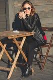 Jeune belle femme de sourire en verres ronds buvant du café Photographie stock libre de droits