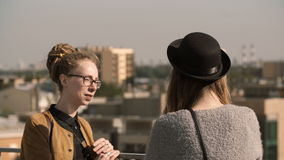 Jeune belle femme deux se tenant sur le balcon, regardant sur le panorama et parlant dans le jour lumineux ensoleillé banque de vidéos