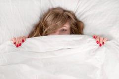 Jeune belle femme drôle se situant dans le lit sous la couverture photo libre de droits