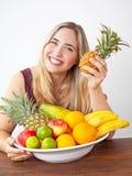 Jeune belle femme en bonne santé avec un bol de fruit exotique frais image libre de droits