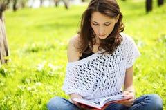 Jeune belle femme en parc d'été lisant un livre photos stock