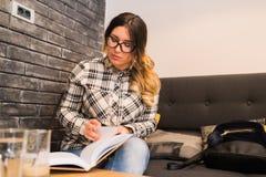 Jeune belle femme en verres lisant le livre intéressant dans le CAM Photo libre de droits