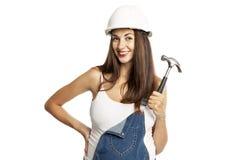 Jeune belle femme enceinte dans un casque avec un marteau dans sa main D'isolement sur un fond blanc photos libres de droits