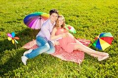 Jeune belle femme enceinte en bonne santé avec son mari et pluie Photographie stock