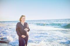 Jeune belle femme enceinte heureuse dans la robe bleu-foncé touchant son ventre avec l'amour et soin marchant et sur la plage Dét Photos stock