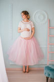 Jeune belle femme enceinte posant près de la fenêtre Photo stock