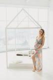 Jeune belle femme enceinte tenant la fenêtre proche à la maison Photographie stock libre de droits