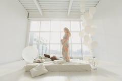 Jeune belle femme enceinte tenant la fenêtre proche à la maison Images stock