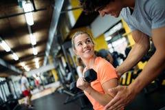Jeune belle femme faisant des exercices avec l'entraîneur personnel image libre de droits