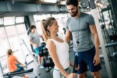 Jeune belle femme faisant des exercices avec l'entraîneur personnel Images stock