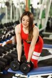 Jeune belle femme faisant des exercices avec l'halt?re dans le gymnase L'heureuse fille de sourire appr?cie avec son processus de image stock