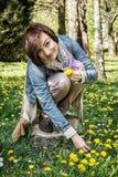 Jeune belle femme faisant le bouquet des pissenlits Photo stock