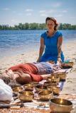 Jeune belle femme faisant le massage de pied avec des cuvettes de chant de Tibétain autour en nature Photos stock
