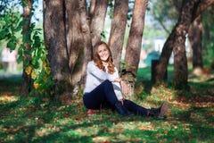 Jeune belle femme Fille d'adolescent de beauté s'asseyant en parc d'automne Image libre de droits