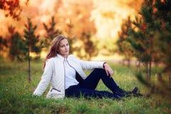 Jeune belle femme Fille d'adolescent de beauté s'asseyant en parc d'automne Images libres de droits