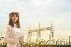 Jeune belle femme futée d'ingénieur électrique travaillant utilisant le comprimé pour vérifier les grilles d'alimentation à l'usi photo stock