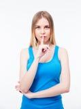 Jeune belle femme gardant le doigt sur ses lèvres Photographie stock libre de droits