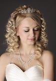 Jeune femme habillée en tant que jeune mariée sur un gris. Photographie stock libre de droits