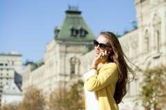 Jeune belle femme heureuse appelant par le téléphone à Moscou Image stock