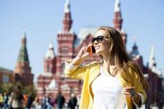 Jeune belle femme heureuse appelant par le téléphone à Moscou Photo libre de droits