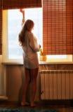 Jeune belle femme heureuse blonde près de la fenêtre Images libres de droits