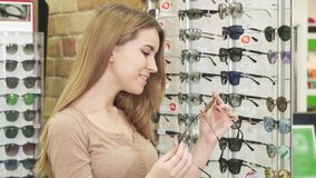 Jeune belle femme heureuse choisissant entre deux paires de lunettes de soleil banque de vidéos