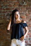Jeune belle femme heureuse dans des vêtements sport contre le mur de briques images stock