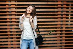 Jeune belle femme heureuse en tissus occasionnels contre le mur Photos stock