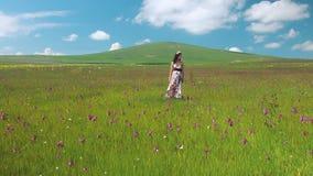 Jeune belle femme heureuse restant dans la longue robe de pré flottant sur le vent Jolie fille de smilind en guirlande de fleur clips vidéos