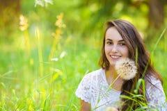 Jeune belle femme heureuse s'asseyant sur l'herbe avec l'écoulement de pissenlit Photographie stock libre de droits
