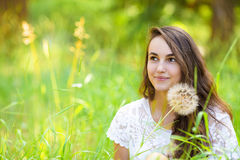 Jeune belle femme heureuse s'asseyant sur l'herbe avec l'écoulement de pissenlit Images libres de droits