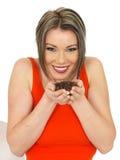 Jeune belle femme heureuse tenant les grains de café fraîchement rôtis Image stock