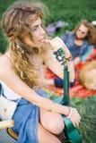Jeune belle femme hippie de cheveux bouclés avec la guitare dehors Photo stock