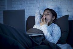 Jeune belle femme hispanique d'intoxiqué d'Internet sur le lit avec le baîllement d'ordinateur portable d'ordinateur fatigué photos libres de droits
