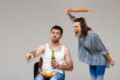 Jeune belle femme irritant avec de la bière potable de l'homme, le football de observation Photos libres de droits