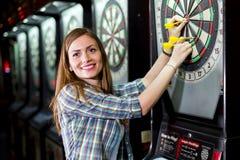 Jeune belle femme jouant des dards dans un club photo libre de droits