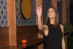 Jeune belle femme jouant des dards dans un club image stock