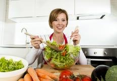 Jeune belle femme à la maison de cuisinier à la cuisine moderne préparant le sourire végétal de saladier heureux Images libres de droits