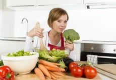Jeune belle femme à la maison de cuisinier à la cuisine moderne préparant le sourire végétal de saladier heureux Images stock