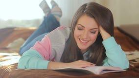 Jeune belle femme lisant un livre attentivement et ayant l'amusement Sourire mignon d'un modèle gentil Brunette avec des œil bleu clips vidéos