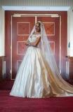 Jeune belle femme luxueuse dans la robe de mariage posant dans l'intérieur luxueux Jeune mariée élégante magnifique avec le long  Photos libres de droits