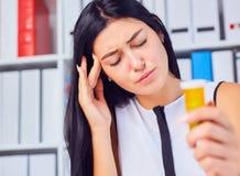 Jeune belle femme malade fatiguée s'asseyant dans le lieu de travail dans le bureau tenant la bouteille avec des pilules Sentimen image libre de droits