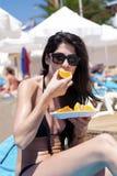 Jeune belle femme mangeant du fruit orange frais à la plage Image stock