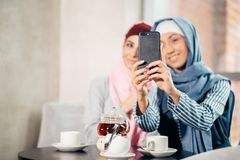 Jeune belle femme musulmane prenant un autoportrait avec le téléphone d'appareil-photo Image stock