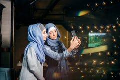 Jeune belle femme musulmane prenant un autoportrait avec le téléphone d'appareil-photo Photos stock