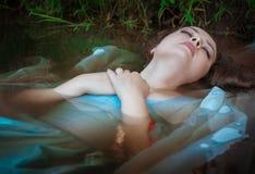 Jeune belle femme noyée se situant dans l'eau image stock
