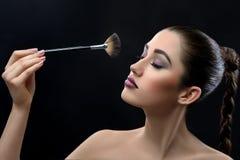 Jeune belle femme portant le maquillage professionnel tenant le maquillage Photographie stock libre de droits
