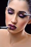 Jeune belle femme portant le maquillage professionnel tenant le maquillage Photographie stock