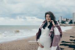 Jeune belle femme pragnant posant près de la mer à la plage Images stock