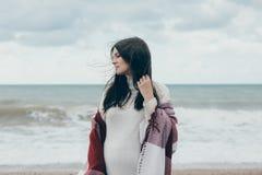 Jeune belle femme pragnant posant près de la mer à la plage Photo stock